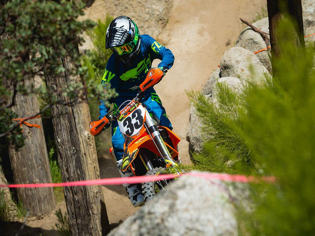 2019 KTM 350 XC-F weaving between boulders and trees.