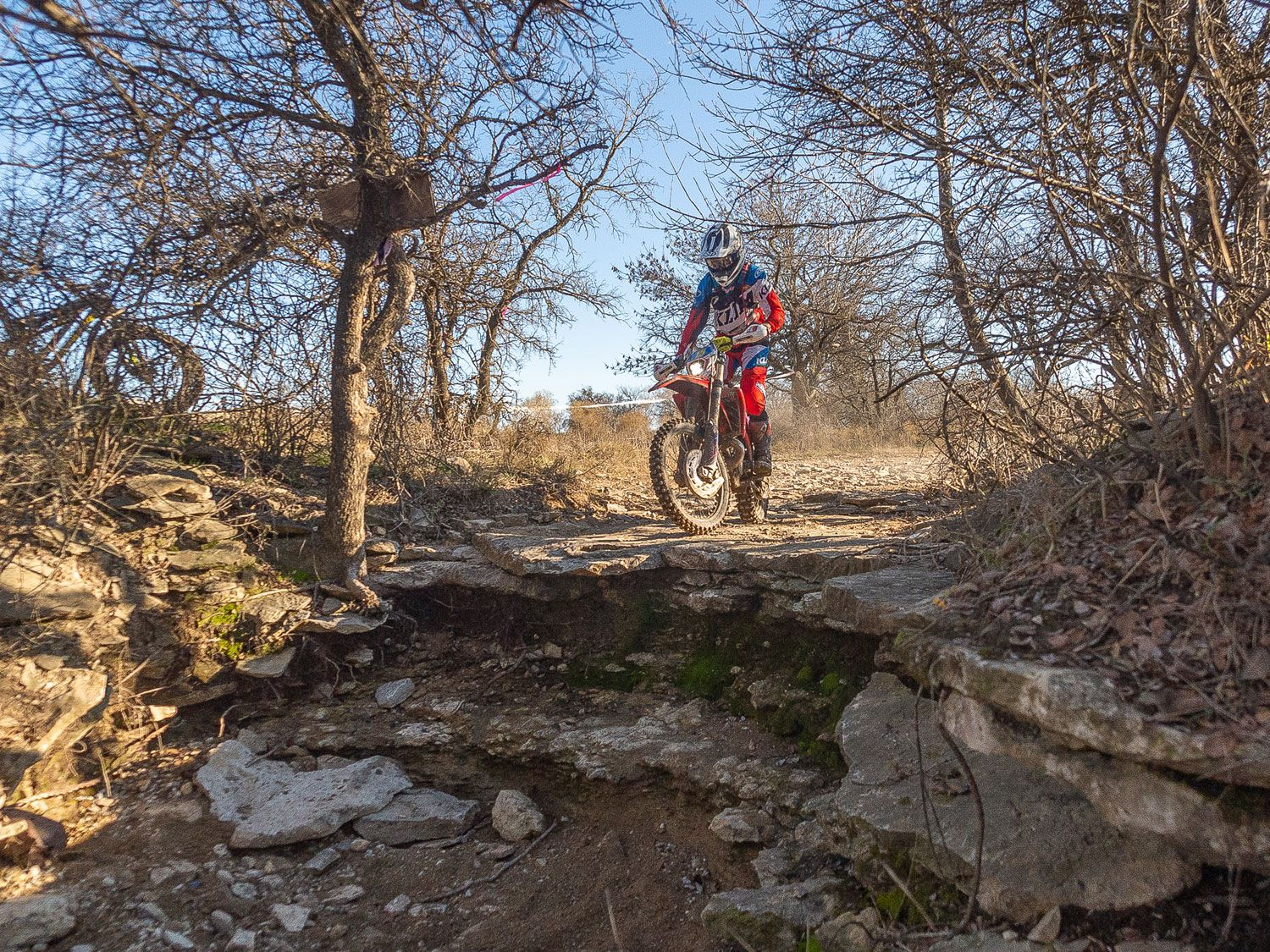 Beta USA's Max Gerston approaches a ledge at the 2019 Red Bull Override hard enduro race in Decatur, Texas. Because this drop-off has very little runout, he's using first or second gear for it.